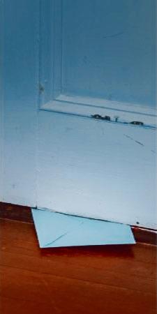 Enveloppe glissée sous une porte